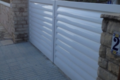 Fabricación e instalación de puerta de aluminio soldada y lacada blanca con lamas de avión de 150 mm en Urb. San Miquel de Miami Platja